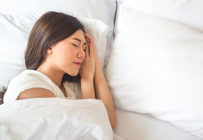 Beautiful asian woman sleeping on white bed with happy feeling