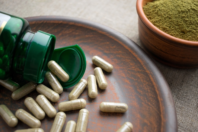 Close up Green capsules, bottle and powder on a clay brown plate on a burlap background