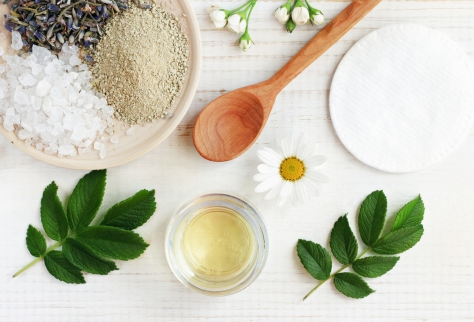 Cosmetic oil, clay, sea salt, herbs, plant leaves. Facial treatment preparation background.
