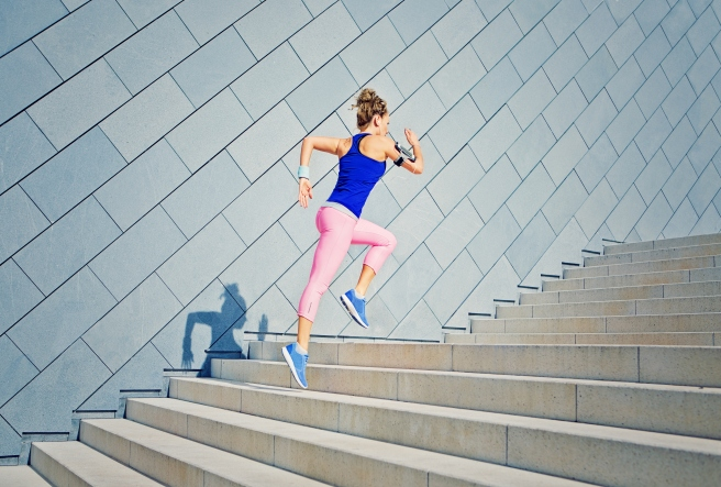 Girl is runing on the city stairs and listening the music