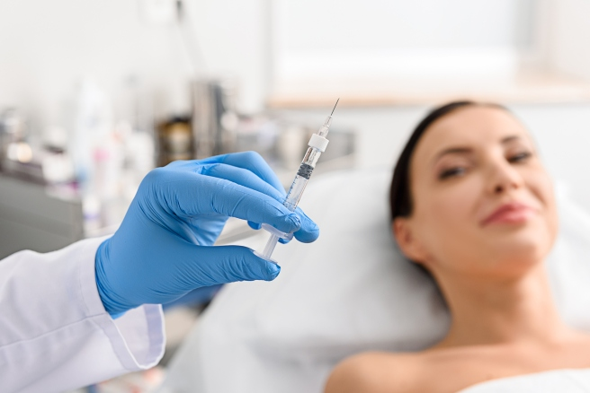 Physician arm holding injector in cosmetology clinic