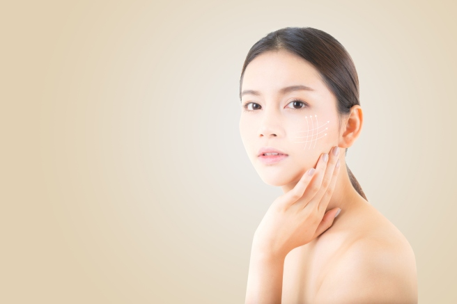 Portrait of beautiful asian woman makeup of cosmetic, girl hand touch cheek and smile with arrow antiaging, face of woman beauty perfect wellness on yellow background with skin healthcare concept.
