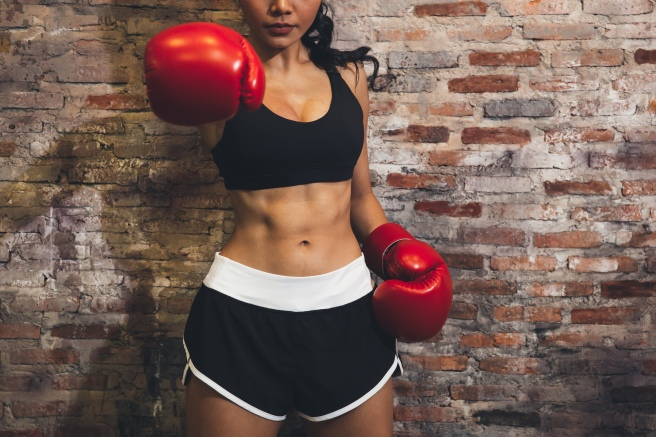 Female muscular sport boxer with boxing gloves posing over wall brick background