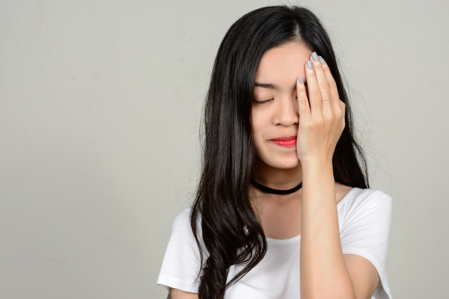 Young beautiful Asian woman against white background