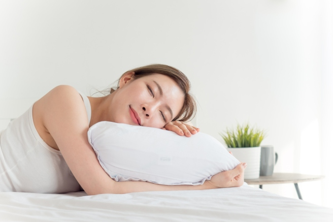 Young beautiful asian woman sleeping happy on white bed with happy feeling
